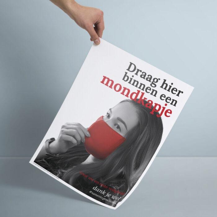 Poster vrouw met rood mondkapje en tekst 'Draag hier binnen een mondkapje' #samentegencorona